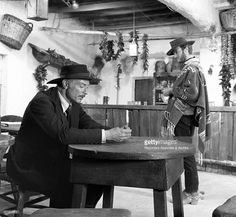 American actor Lee Van Cleef with American actor <a gi-track='captionPersonalityLinkClicked' href=/galleries/search?phrase=Clint+Eastwood&family=editorial&specificpeople=201795 ng-click='$event.stopPropagation()'>Clint Eastwood</a> in the movie For a Few Dollars More, directed by Sergio Leone. The former is sitting at a saloon table while the latter, standing, is looking at him. 1965