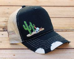 10b8d58097ca9 Grab this black and tan hat with embroidered cactus and cow skull