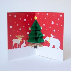 """The front of this card is meant to look like a storybook. But open it and find a darling little tree pop-up made of honeycomb paper! Gold embossed lettering on front says """"We Wish You A Merry Christma"""