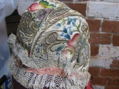 $50 US  baby's cap embroidered with flowers and fruit in coloured silks and metal thread. Original: probably mid-18th century