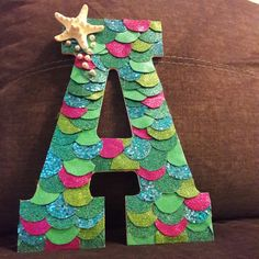 DIY Mermaid letter for baby nursery! So glad I finally finished it :). Made from glitter scrapbook paper and glitter foam paper from the craft store, plus hot glue. Use a bottle cap to trace out the semi circles and cut to fit ! Mermaid Crafts, Mermaid Diy, Baby Mermaid, Mermaid Birthday Party Decorations Diy, Mermaid Baby Shower Decorations, Diy Gifts For Kids, Diy For Girls, Mermaid Bedroom, Mermaid Nursery Theme