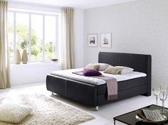Dieses schwarze Boxspringbett aus Kunstleder mit weißen Nähten passt durch die schlichte Eleganz in jedes Schlafzimmer.