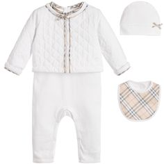 Baby girls white babygrow, jacket, hat and bib gift set by Burberry. Made with soft cotton jersey, this footless babygrow has a Peter Pan collar, with the designer's pale beige, new classic check. It has buttons on the back and it fastens with poppers between the legs. The quilted, lightly padded jacket has poppers and is trimmed with check. The checked bib is made with smooth cotton with a towelling back and fastens with a popper. The jersey hat has a bow appliqué and the set comes in a…