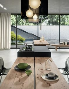 Kitchen:Dark Kitchen Island Mix With Extended Wooden Dining Table Glossy Black Chairs White Marble Floor Glass Black Range Hood With Pendant Lights Inside Wooden Bench White Curtain Big Glass Window Futuristic Contemporary Kitchens: With Innovative Design