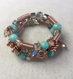 Memory wire bracelet made with handmade copper coiled-wire beads, turquoise and crystal beads. Attention to detail with small dangles on each end.   DragonflyDesigns4.13@gmail.com, $15, shipping included.