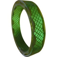 A gorgeous transparent green carved vintage bakelite bangle with gold accents. Straight wall, lattice carving on the inside plus there are carved long, pointed ovals which are gold color and reflect on the sides as scallops.