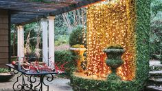 Hang Twinkling Lights - 101 Fresh Christmas Decorating Ideas - Southern Living - Hang twinkling Christmas lights on a fountain or stone wall in the garden to create a striking winter focal point from your patio or porch. Even if it's too cold to entertain outside, you''ll enjoy the soft cozy glow through the windows.