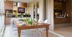 O estilo contemporâneo ficou evidenciado pela utilização de cadeiras de acrílico e pelo uso dos tijolos no espaço gourmet. Projeto da arquiteta Camila Klein.