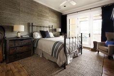 Tonos cálidos, con mobiliario de madera y metal, en este dormitorio.