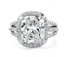A gorgeous cushion cut diamond with a diamond halo and more diamonds pave set along the triple shank.