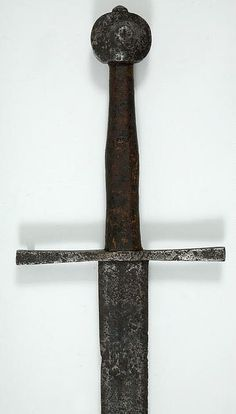 Hand-and-a-half Sword      Dated: circa 1250 — 1350     Place of Origin: Germany     Medium: steel, copper, leather, wire     Technique: sword, cast, with either inlaid copper or latten decoration, or incised cross decoration     Measurements: overall length, 115 cm; blade length, 89.5 cm; blade width at hilt, 4.9 cm; grip width, 28.5 cm; cross width, 30.5 cm; pommel diameter, 6 cm; pommel depth, 15 cm; weight, 1.40 kg