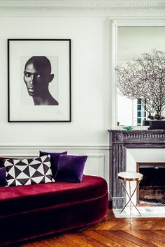 A richly upholstered velvet sofa, another Huynh creation, adds a vibrant burst in a black-and-white corner of the living room | archdigest.com