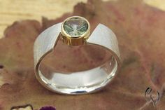 Unusual, wide ring of silver. In the slanted opening of the ring, a yellow gold version has a 6 mm green tourmaline in the Kaleidoskopschliff. The surface is Matt scratched, the sides and the mount are polished The ring is 7 mm wide and has the Ringweite Modern Jewelry, Metal Jewelry, Jewelry Rings, Jewelery, Silver Jewelry, Craft Jewelry, Bijoux Design, Schmuck Design, Jewelry Design