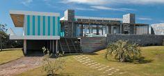 Concreto, pedras e madeira – além das faixas azuis da fachada – trazem alto-astral a este refúgio em Punta Del Este