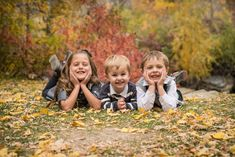 T.C. MARTINSEN Photography: ANDERSEN    family young kid siblings laying on ground pose fall family portrait session in yellow fall leaves. family of five with young kids in Utah location standing in trees and on path siting in leaves and grass