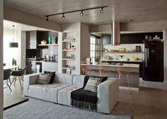 Decoração contemporânea com toque retrô e elementos industriais com ambientes integrados. Na sala sofá branco, tapete.