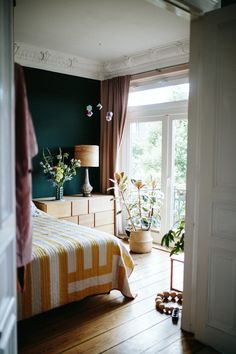 Dark green wall, brown and yellow accents in the bedroom / Herz & Blut.