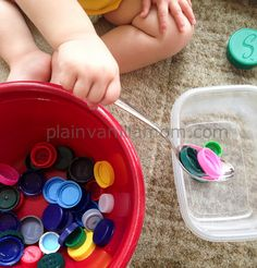 Scooping Bottle Caps for Toddler Play. I have a similar activity in my book - My Toddler Talks: Strategies and Activities to Promote Your Child's Language Development. I use plastic ice cubes instead of bottle caps. So much fun for toddlers!