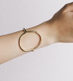 Textured with a series of hashmarks on the surface, this open oval cuff is a large, statement-making piece.