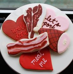 "Meat cookies for men. Decorated to look like bacon, ham, and a t-bone steak. The hearts say ""well done,"" ""let's pork,"" and ""meat me."""