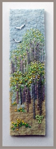 On a needlefelted backgound, Jo Woods has used beads for the trees and added hand stitching. The trees could be added using cords and french knots