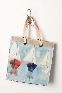Crafted by affixing a vintage oil painting atop repurposed canvas pouches, this handmade, one-of-a-kind tote gives new life to a forgotten masterpiece. By Leslie Oschmann for Swarm.