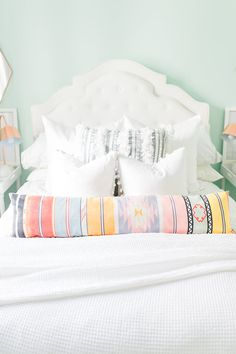 Bright bedroom with teal walls, white bedding and a printed throw pillow