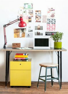 simple desk in front of window, pin boards to right and left, low storage