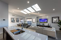 Love the skylights in this open-plan living, dining and kitchen area!