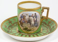 Antique Royal Vienna Hand painted cup and saucer set. Cup has hand painted scene depicting the Battle at Heilsberg, signed Jovy. The saucer has a hand painted scene depicting the Coronation of Napoleon I, signed David. Each has a gilded border design on green background. Has Gold Crown over N mark to bottom of both pieces. This mark is similar to Naples marks. However there is speculation the decorator may be Sevres. The original wares were provided by Royal Vienna, Austria. Blue underglaze…