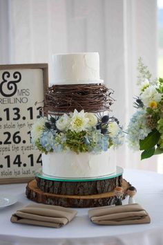 Love this rustic cake with butter cream icing, a layer of woven branches, fresh pale blue flowers and a tree stump as a pedestal.  Photo by Katy Trefry Photography Pinned from www.dreamweddingspa.com
