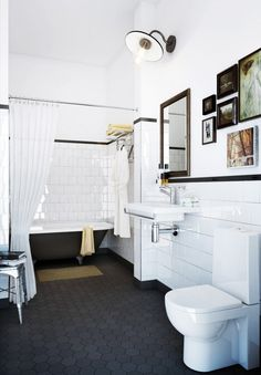 6x6 square tile with charcoal grout, black square strip around top. Black hex floor tile with a claw foot tub and art on the walls