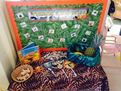 Handa's surprise interest table. Real fruit, animal masks, wooden African animals, key words and book.