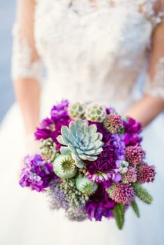 bridal bouquet by designer Sharon Duke of Isn't She Lovely Florals – Florida, with succulents, poppy pods, purple carnations, bullet allium,...