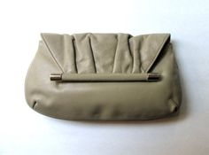 Vintage 60s taupe leather clutch bag with ruched flap & metal leather-covered bar. Medium sized & under the flap is a snap closure. Faille fabric lining with a metal zippered pocket. The color is most like the first photo. The label is Margolin. 11.5 at widest x 6.5 high x 1.5 deep at bottom  Very good vintage condition, gentle wear & creasing to the leather, a small red stain (lipstick?) see last photo, the rest of the lining is clean with a few marks here & there, the gold m...