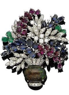 A gem-set and diamond giardinetto brooch The oval cabochon black opal vase accented by single-cut diamonds, issuing sprays of flowers set with rows of pear-shaped rubies, marquise-cut sapphires, to further pear-shaped emerald accents, single and brilliant-cut diamond leaves, diamonds approx. 1.25cts total, length 5.5cm