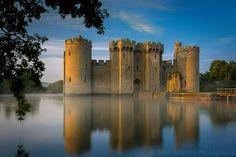 Bodiam Castle, Bodiam, England. This beautiful medieval castle built in 1385 is situated in East Sussex, in southern England.  Here, the early morning mist is beginning to lift as the first rays of sunrise light up the ancient stone walls.