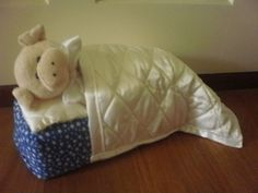 Lazy piggy in a blue bed doorstop made by Sheila.