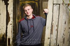 Senior boy with old doors taken in our backyard studio. Copyright canazziphoto.com.