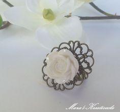 Du erhälst einen wunderschönen verschnörkelten Ring im Vintagelook mit dem Motiv einer weißen Rose. Der Ring ist verstellbar und in antik bronze ge...