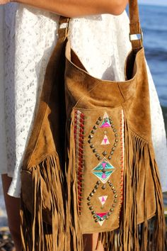 Fringed tan suede cross body with stud and native embroidery detail. Via Nuria López.