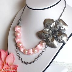 "Handmade bib/choker style silver vintage flower pendant, chain, and pink ribbon and pearl necklace. The flower is layers of silver vintage flowers and the pearls are intertwined with a pink ribbon. Necklaces closes with a lobster clasp at the back.    Length: Approx 10"" long (If you desire more length, no problem, at checkout please state in the ""Note to Seller"" section how much extra length you would like)    Flower Pendant: approx 3"" x 3"""