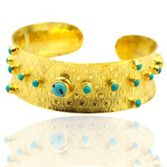 The Stylish Bracelet cuff feature 19 Turquoise cabochon gemstones, hand-cut for custom design. Set in 18 carat yellow gold plated Brass with Nice pattern.
