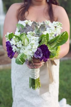 A mixture of purple lisianthus, white stock / Gilly flower, and succulents, surrounded by over-sized leaves -- perfect for a spring wedding!