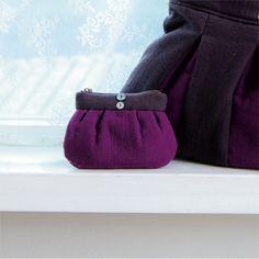 タックを入れたデザインに、紫色の濃淡が小粋に映えるバッグとポーチのセット。 中央につけた貝ボタンが涼やかなアクセントになっています。