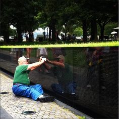 A friend snapped a shot of an elderly man crying as he located his loved ones' names on the memorial and traced over them. I want to give him a hug. - Imgur