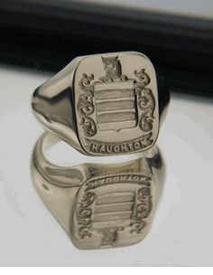 $349.99 Cushion Shape. Large Sized. Deep engraving.  Features: Coat of Arms on the Shield, Family Crest (above the helmet), Traditional Decorative Mantling, and the Family Name in raised letters on the ribbon.  This ring is engraved by our highly qualified craftsmen to feature your own unique Family Crest / Coat of Arms.  This ring makes a wonderful & unique presentation or heirloom gift, one that will be worn with pride and treasured forever.