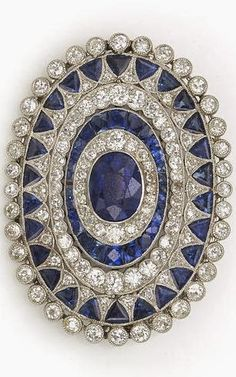 An art deco sapphire and diamond brooch, circa 1925 centering an oval-shaped sapphire framed with several successive rows of old European and single-cut diamonds and calibré and triangular-cut sapphires; central sapphire weighing approximately: 2.50 carats; estimated total diamond weight: 2.60 carats; mounted in platinum. Google+