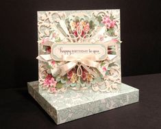 This is one incredibly bedecked birthday card, adorned with layers upon ever more layers of all manner of charming and dramatic froufrou! Creating the card along with its coordinating dimensional envelope was certainly a very time-intensive endeavor, which is reflected in the higher price Ive assigned to the card. The spectacular patterned papers featured on this card are part of stationer/designer Anna Griffins smashing new Fancy Florals Collection; I can only hope Ive done them justice…