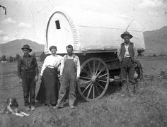 Three men, a woman and their dog next to their covered wagon in 1878. (Photo Courtesy Utah State Historical Society)